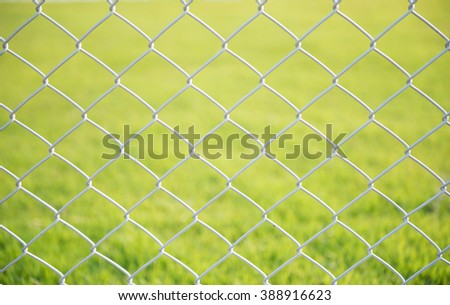 wire mesh steel with green grass background - stock photo