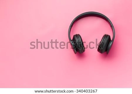 wireless headphones on pink background - stock photo