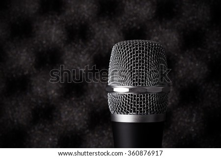 Wireless microphone closeup on foam rubber acoustic treatment background - stock photo