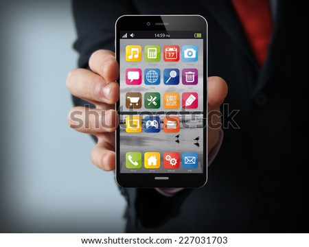 wireless, mobility and communications concept: businessman hand holding a phone with interface on the screen  - stock photo