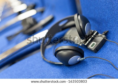 wireless multy language headphones set on the chairs in conference room - stock photo