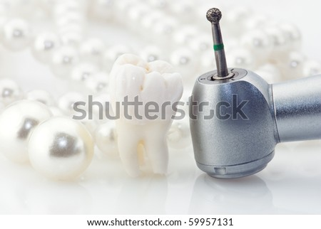 Wisdom tooth natural pearls and dental drill. - stock photo