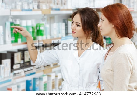Wise choice. Shot of a young pharmacist showing her client medical products at her pharmacy. - stock photo