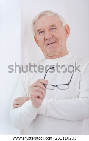Wise handsome. Cheerful senior man keeping arms crossed and smiling at camera while leaning at the wall - stock photo