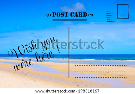 Wish You Were Here summer vacation postcard with scenic ocean beach view - stock photo