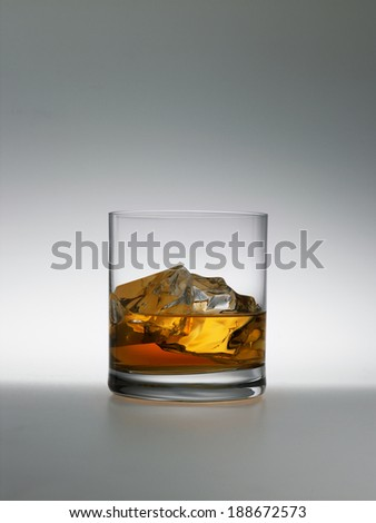 wiskey wiht ice in clear glass on a grey background - stock photo