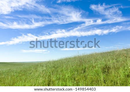 Wispy clouds, deep blue sky, and green grass with rolling hills are what you'll find at the Kansas Tallgrass Prairie Preserve. - stock photo