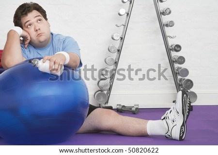 Wistful overweight Man sitting on floor with exercise ball in health club - stock photo