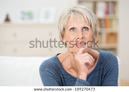 Wistful senior woman sitting thinking staring pensively up into the air as she reminisces on her life - stock photo