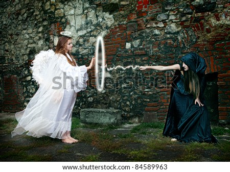 witch and angel magical battle between - stock photo