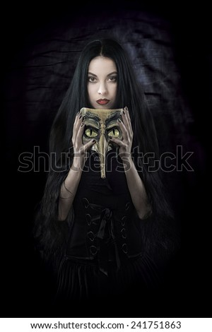 Witch holding a mask - stock photo