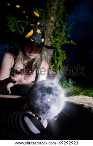 Witch holding glowing moon and telling the spell - stock photo