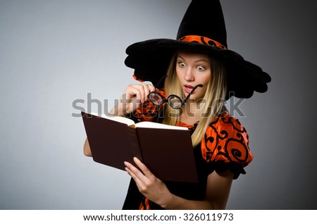 Witch with book in dark studio - stock photo