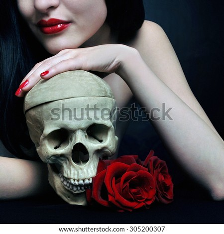 Witch with skull and roses - stock photo