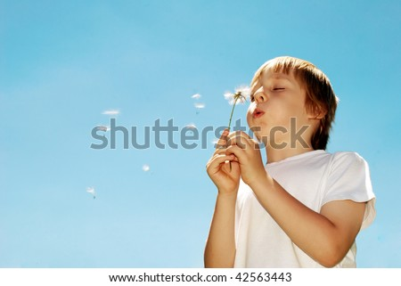 With dandelions in hands against the sky - stock photo
