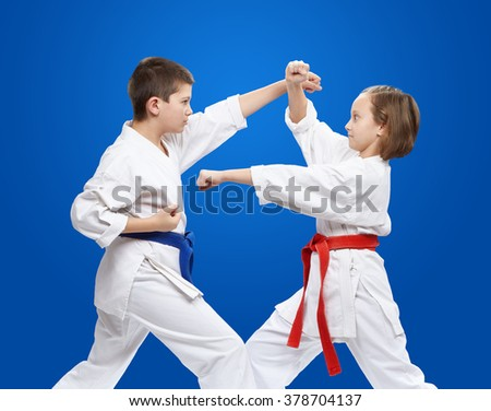 With red and blue belt athletes train kicks and blocks karate - stock photo