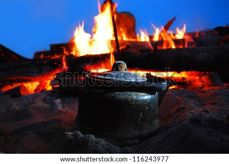 with smoke pot on the fire in the evening - stock photo