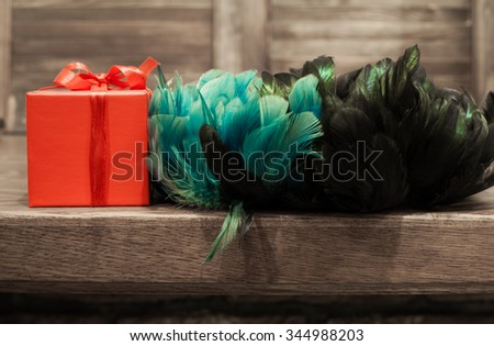 with turquoise, blue, green and black feathers and red box on a wooden background. Necklaces - stock photo