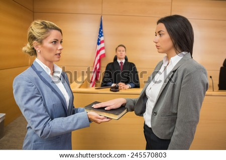 Witness taking an oath in the court room - stock photo