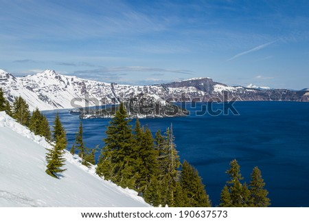 Wizard Island in Crater Lake national park in Oregon early spring with some snow left from winter - stock photo