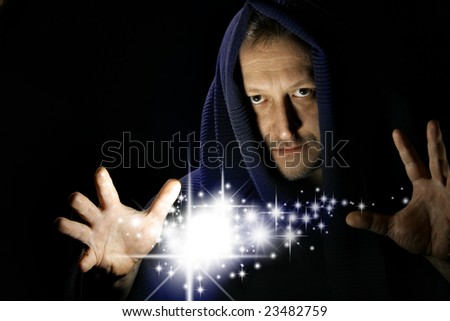 Wizard witg glowing stars between your hand - stock photo