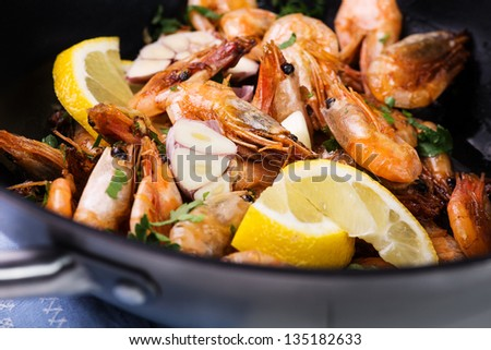 wok stir fry with shrimps, lemon, garlic and parsley - stock photo