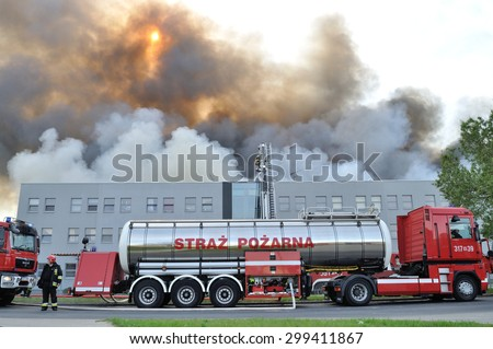 Wolka Kosowska, Poland - May 10, 2011: Water tender fire truck, during extinguish a raging fire in a China Mart storehouse. The fire burned 150 storage units covering nearly 2 hectares. - stock photo