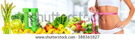 Woman abdomen with measuring tape over vegetables background. - stock photo