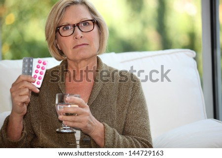 Woman about to take her medication - stock photo