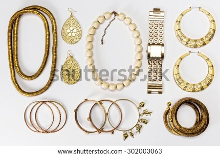 Woman accessories,gold and yellow,against white background.Top view. - stock photo