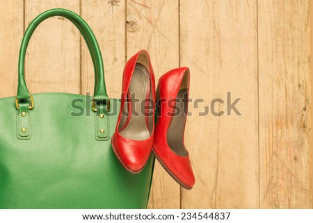 Woman accessories on wood background, green handbag and red stileto - stock photo