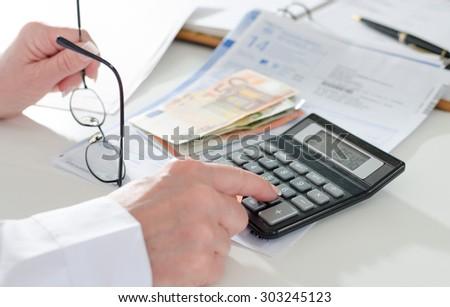 Woman accountant calculating taxes - stock photo