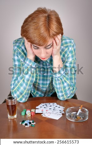 Woman addicted to vice. Depressed and sad woman sitting at the table and holding her head thinking about her addiction to alcohol, gambling and smoking  - stock photo