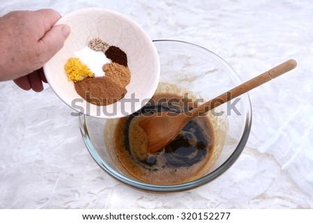 Woman adding spices - cinnamon, ginger, nutmeg, cloves, salt and lemon zest - to pumpkin pie filling - stock photo
