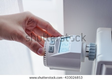 Woman adjusting temperature of home heater in room - stock photo