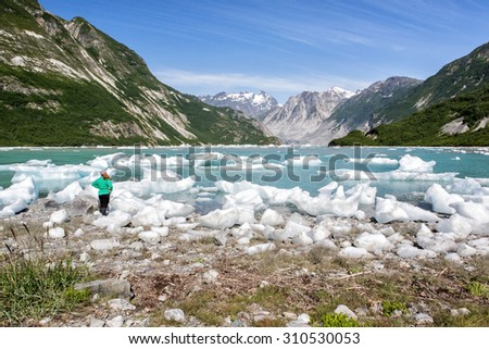 Woman admires ice and mountain beauty of McBride Inlet in Glacier Bay - stock photo