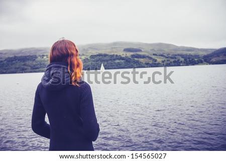 Woman admiring stillness of the lake - stock photo