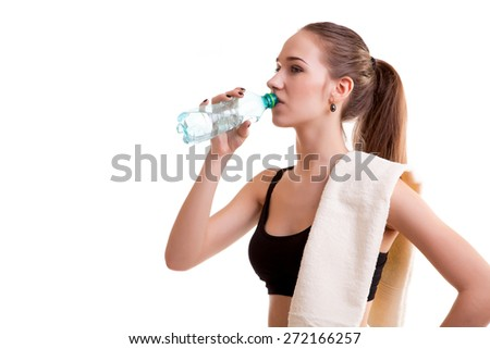 Woman after sport drinking water from bottle with towel on shoulder isolated over white background - stock photo