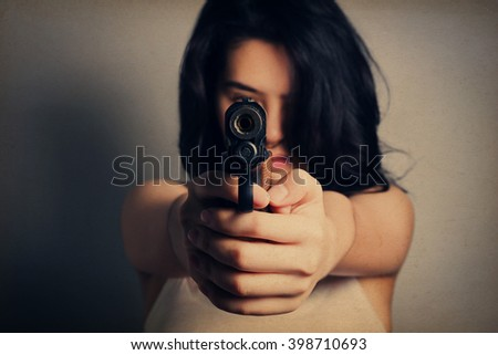 Woman aiming a gun,focus on the gun, grunge vintage style. - stock photo