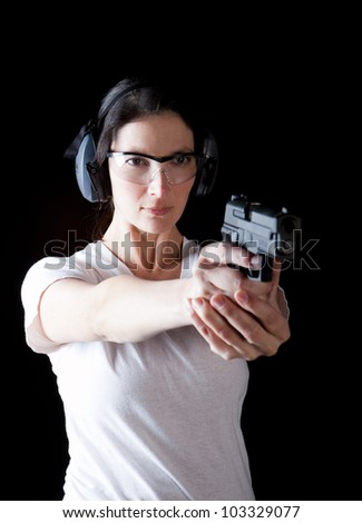 Woman aiming a gun with protective gear - stock photo