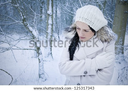 woman alone and cold in forest covered by snow landscape - stock photo