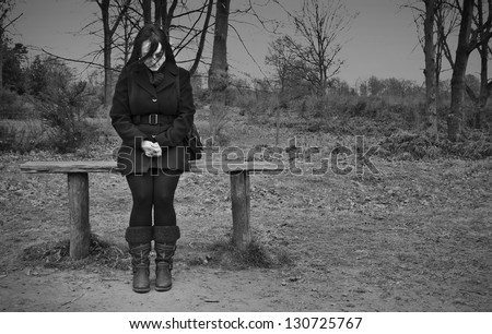 woman alone on park bench looking sad, black and white landscape - stock photo