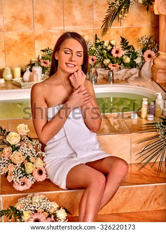 Woman among the flowers relaxing at water spa. - stock photo