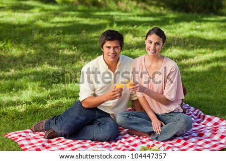 Woman and a man looking straight ahead of them while touching glasses of orange juice during a picnic - stock photo