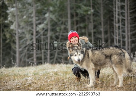 Woman and Alaskan Malamute walk in autumn forest. focus on woman, copy space - stock photo