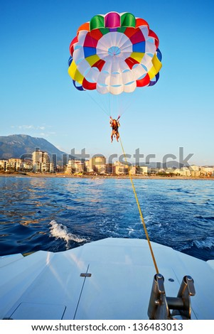 Woman and boy fly on glider over sea - stock photo