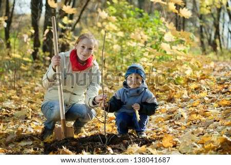 woman and boy with spade outdoors planting  tree in autumn - stock photo