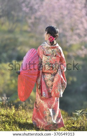 Woman and cherry blossoms of the Japanese kimono - stock photo