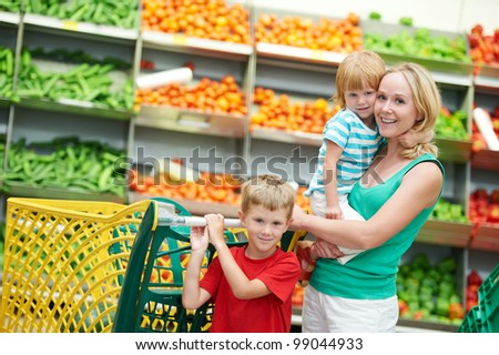 woman and child girl with shopping cart in fruit vegeable department of supermarket store - stock photo