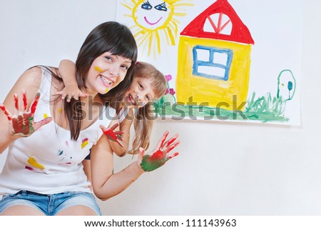 Woman and child have fun paint colors - stock photo